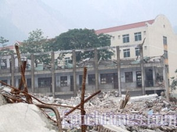 The new school building was leveled to ruins while the building being classified as 'dangerous' before the earthquake in the far background remained standing. (The Epoch Times)